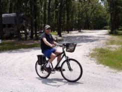 Full time RV resident riding bike through Providence RV Park near Lake Fork TX.